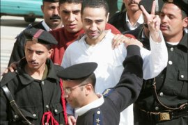 afp – Mohammed Essam Ghoneim al-Attar (C) flashes the victory sign as he is escorted by policemen to an underground entrance