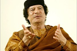 REUTERS/  Libyan leader Muammar Gaddafi gestures during his debate with two Western scholars in the desert in Sebha March 2, 2007, in a move apparently designed to further the resumption of international ties following years of isolation. Speaking on the 30th anniversary of his declaration of a Jamahiriyah or state of the masses, Gaddafi said Libya was embracing globalisation and the outside world after years of