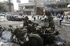 r_The wreckage of a vehicle used in a car bomb attack lies on a road in Baghdad April 15, 2007. The attack which targeted a police patrol killed five people and wounded
