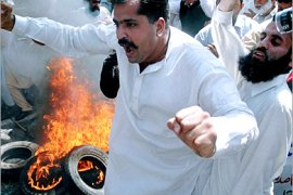 AFP  /  Activists of Pakistani political opposition parties chant slogans beside burning tyres during an anti-Musharraf demonstration in front the Supreme Court building in Islamabad, 13 April 2007, where suspended Chief Justice