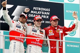 . AFP /   First placing Spanish Formula One driver Fernando Alonso (C) of McLaren-Mercedes with second placing team-mate British driver Lewis Hamilton (L) and Finnish driver Kimi Raikkonen of Ferrari pose at the podium during Malaysian Grand Prix, in Sepang International Circuit 08 April 2007.
