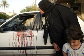 f_An Iraqi woman peeps inside a blood stained car of two women allegedly shot dead by private security guards in central Baghdad, 09 October 2007. Foreign security guards