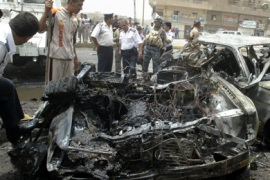 A US soldier and Iraqi police look at destroyed vehicles at the scene following a car bomb which targeted a passing Iraqi army patrol in the Karada Kharej area of southern Baghdad on June 9, 2008.