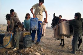 AFP PHOTO/Iraqi children fill jerry cans with water before hauling them away on a donkey at a well in Taji, 30 kms outside Baghdad, on June 29, 2008.