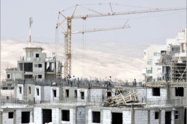 AFP  / Backdropped by the Judean Desert in the West Bank, laborers work on a building in Maale Adumim, the largest Jewish settlement in the Palestinian territories, on August 27,