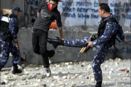 r : A member of the Palestinian security forces (R) kicks a Palestinian stone-thrower, protesting Israel's offensive in Gaza, in the West Bank town of Bethlehem January 8, 2009.