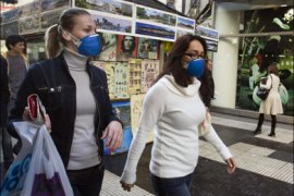 r : Women wearing protective masks to avoid getting the H1N1 flu virus walk by on a Buenos Aires street, July 7, 2009. Argentines are questioning the government's handling of an