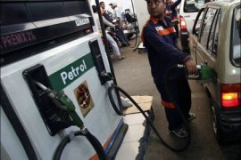 r : An employee fills a car with petrol at a gas station in Jammu July 1, 2009. The government unexpectedly raised gasoline and diesel prices by as much as 10 percent on