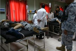 Medics treat Iraqi soldiers after they were wounded in an improvised explosive device (IED) that targeted their patrol in the northern city of Kirkuk on August 17, 2009