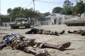 REUTERS/African Union Mission to Somalia (AMISOM) tanks drive past dead bodies after fighting in the streets of the capital Mogadishu,