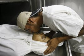 A Palestinian youth says a final farewell to a Palestinian killed by Israeli fire in the town of Beit Lahia in the northern of Gaza Strip on August 24, 2009