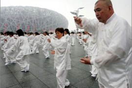 "Some 34,000 people dressed in white silk perform ""taiqiquan,"" or martial arts shadow boxing, to mark the first anniversary of the Beijing Olympics, in Beijing on August 8, 2009"