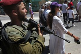 AFP \An Israeli soldier secures a group of Jewish French tourists during their pilgrimage to the Tomb of the Patriarchs, holy to both Jews and Muslims, in the West Bank city of Hebron on August 19, 2009