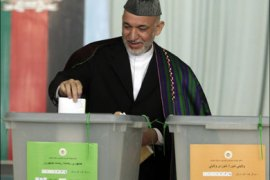 r : Afghan President Hamid Karzai casts his vote in the presidential election in Kabul August 20, 2009. Streets in Afghanistan were mainly quiet and tense early on Thursday