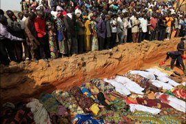 r_Villagers look at bodies of victims of religious attacks lying in a mass grave in the Dogo Nahawa village, about 15 km (9 miles) to the capital city of Jos in central Nigeria, March
