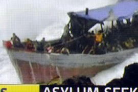 A Channel 7 TV framegrab of a photo released by The West Australian on December 15, 2010 shows a survivor (C) from an asylum boat full of refugees which was smashed by violent seas against the jagged coastline of Australia's Christmas Island