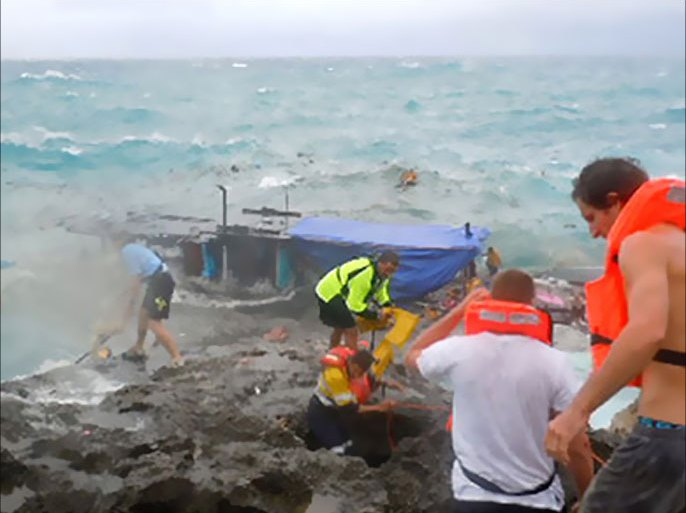 Residents and police (R) try to rescue refugees from an asylum boat (C) being smashed by violent seas against the jagged coastline of Australia's Christmas Island on December 15, 2010.