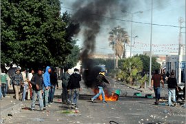 "Tunisian demonstrators move along a street during clashes with security forces in Regueb, near Sidi Bouzid on January 10, 2011.  Tunisian President Zine El Abidine Ben Ali blamed weekend rioting that left at least 14 people dead on ""gangs of thugs"","