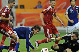 Jordan's goalkeeper Amer Sabbah (bottom-R) tries to block an attempt by Japan's defender Atsuto Uchida