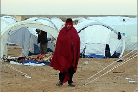 epa02609044 An Egyptian refugee from Libya walks at a military field hospital run by the Tunisian army at the Ras Jdir border post, near the Tunisian city of Ben Guerdane,