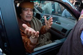 Libyan leader Muammar Gaddafi waves from a car in the compound of Bab Al Azizia in Tripoli, after a meeting with a delegation of five African leaders seeking to mediate in Libya's conflict, April 10, 2011. Gaddafi, making his first appearance in front of the foreign media in weeks, joined a visiting African Union delegation at his Bab al-Aziziyah compound in Tripoli on Sunday.