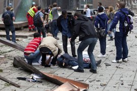 epa02836954 Local workers rush to the aid of an injured person following the explosion in the centre of Oslo 22 July 2011.    Twin bomb and shooting attacks took place in the