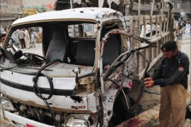 A Pakistani policeman inspects the wreckage of a police van following a bomb explosion in Peshawar on August 11, 2011