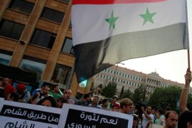 "Activists carry banners and wave a Syrian national flag during a protest in solidarity with Syria's anti-government protesters, in front of the U.N. headquarters and the government palace in Beirut August 15, 2011. The banner on right reads: "" Yes to the Syrian people's revolution""."