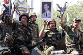 Syrian soldiers raise their weapons while holding a picture of Syrian President Bashar al-Assad as they leave the eastern city of Deir Zor following a 10-day military operation on August 16, 2011.