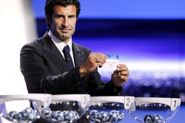 Portuguese football player Luis FIgo shows the name of FC Milan during the draw for the UEFA 2011-2012 Champions League on August 25, 2011 in Monaco. AFP PHOTO SEBASTIEN NOGIER