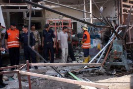 Iraqis inspect damages following twin bomb blasts in the southern city of Kut on August 15, 2011