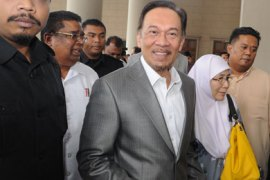 Malaysian opposition leader Anwar Ibrahim (C) arrives at court with his wife Wan Azizah (centre R) in Kuala Lumpur on August 8, 2011. Anwar was expected to finally take to the stand in his drawn-out sodomy trial.