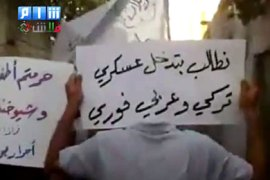 "f_An image grab taken from a video uploaded on YouTube shows Syrian anti-government protesters holding placards that read in Arabic ""we demand an immediate Turkish and"
