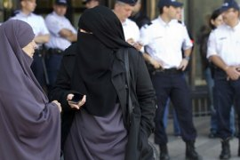 Women wearing niqabs converse as police stand watch in front of the courthouse in Meaux, near Paris, 22 September 2011. The Meaux court, on 22 September, convicted two women for wearing Islamic veils in public – the first conviction since a ban on wearing the veils came into effect in April.