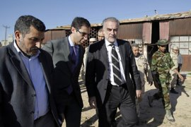 Chief Prosecutor of the International Criminal Court (ICC) Luis Moreno-Ocampo (C) visits the site of a mass grave at the Al-Yarmuk military base in Tripoli on November 23, 2011.
