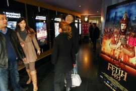 "Turkish filmgoers are pictured next to a poster of ""Fetih 1453"" or ""Conquest 1453"", depicting the conquest of Istanbul by Ottoman Turks at a cinema in Ankara on February 27, 2012. Since it was first screened on February 16 at a symbolic time of 14:53, some 2.5 million viewers have watched the film, according to Box Office Turkey statistics."