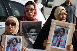 f: bahraini women holding pictures of human rights activist abdul hadi al-khawaja take part 21 november 2004 in a protest in front of a manama court during the trial of al-khawaja, (الفرنسية)