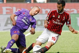 AC Milan's Gianluca Zambrotta (R) fights for the ball with Fiorentina's Houssine Kharja during their Italian Serie A soccer match at the San Siro stadium in Milan April 7, 2012. REUTERS/Alessandro Garofalo (ITALY – Tags: SPORT SOCCER TPX IMAGES OF THE DAY)