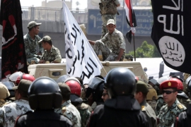 Soldiers stand on a military vehicle next to a Salafist flag as supporters of Salafist leader and former presidential candidate Hazem Salah Abu Ismail and other political parties protest outside the Egyptian military council in Cairo April 28, 2012. Egyptians marched on the country's defence ministry  to demand that the Presidential Election commission be dissolved after it upheld a ban on two Islamist presidential candidates and allowed Hosni Mubarak's former Prime Minister to run. REUTERS