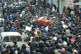 People carry the coffin of late opposition leader Chokri Belaid during his funeral procession which makes its way to the nearby cemetery of El-Jellaz where Belaid is to be buried on February 8, 2013 in the Djebel Jelloud district, a suburb of Tunis.  Thousands of people attend the funeral while Tunis is at a near standstill, with streets deserted, shops shut and public transport at a minimum as a general strike called by a powerful trade union after Bellaid was murdered took effect.  AFP PHOTO / FETHI BELAID
