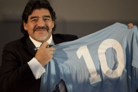 "Football legend Argentinian Diego Maradona kisses a SSC Napoli number 10 jersey during a press conference on February 26, 2013 in Naples. Maradona, who rarely stepped foot in Italy since leaving under a cloud in the 1990s amid claims of collusion with mafia dons and a positive drugs test for cocaine, asked for ""justice"" in his dispute with Italian tax authorities on an emotional trip to Naples — the scene of some of his greatest career successes. AFP PHOTO / CARLO HERMANN"