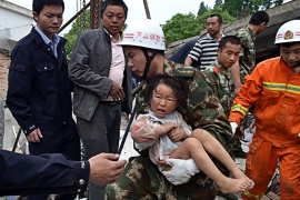 A rescuer (C) carries a child to safety after she was pulled out of her collapsed home after an earthquake hit Ya'an City in Lushan county, southwest China's Sichuan province on April 20, 2013. More than 100 people were killed and 3,000 injured when a strong earthquake shook southwest China on April 20, wrecking homes and triggering landslides in an area devastated by a major tremor in 2008. CHINA OUT AFP PHOTO