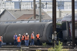 Investigators inspect derailed cars on the site of a train accident in the railway station of Bretigny-sur-Orge on July 13, 2013 near Paris. Rescue workers searched for survivors early Saturday, hours after a high-speed train derailed just south of Paris, killing at least six people and injuring 30 more.  AFP PHOTO / KENZO TRIBOUILLARD