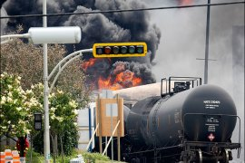 Firefighters walk past a burning train wagon after an explosion at Lac Megantic, Quebec, July 6, 2013. REUTERS/Mathieu Belanger (CANADA – Tags: DISASTER SOCIETY)