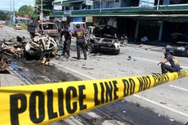 Investigators look for evidence among wreckage a day after a car bomb explosion in Cotabato city, on the southern island of Mindanao, on August 6 2013. The death toll from a powerful bomb that hit the southern Philippine city rose to eight, police said, as officials pointed to political rivalry as a possible motive.