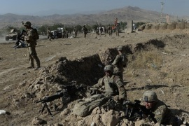 US soldiers keep watch at the site of a suicide attack in Maidan Shar, the capital city of Wardak province south of Kabul on September 8, 2013. At least four Afghan intelligence agents were killed and dozens of civilians were wounded when a group of Taliban militants attacked an intelligence bureau in central Afghanistan, officials said.