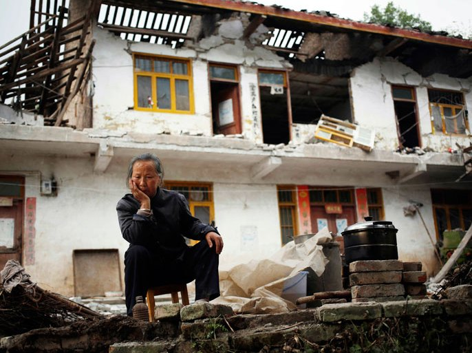 Chinese resident Ri Chenfu sits outside her home damaged by the earthquake in Ya'an, Sichuan Province, China, 21 April 2013. The death toll in the aftermath of a powerful earthquake in south-western China stood at more than 200 on 21 April, as search teams combed remote areas isolated by landslides, state media reported. At least 6,700 people were injured when earthquake struck Sichuan province at 8:02 am, state media said. The China Earthquake Administration (CEA) recorded a magnitude 7.0 earthquake, while the US Geological Survey said it had measured 6.9. EPA/HOW HWEE YOUNG
