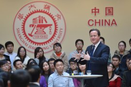 "Shanghai, Shanghai, CHINA : This picture taken on December 3, 2013 shows British Prime Minister David Cameron (R) delivering a speech at Shanghai Jiao Tong University in Shanghai. Britain should recognise it is not a big power but ""just an old European country apt for travel and study"", Chinese state-run media snapped on December 3 as Cameron visited. CHINA OUT AFP PHOTO"