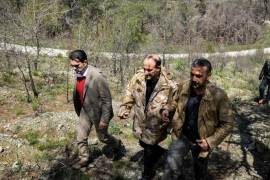In this picture released by the Syrian National Coalition Media Office, Ahmad al-Jarba, center, the head of the delegation of the Syrian National Coalition, who wears a camouflage jacket during his rare visit to the front lines where the rebels fighting against the Syrian government troops, in the coastal province of Latakia, Syria, Tuesday April 1, 2014. Al-Jarba visited Kassab during his trip to the Latakia's front lines, the Western-backed Syrian National Coalition said in a statement. (AP Photo / The Syrian National Coalition Media Office)