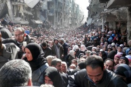 AP10ThingsToSee – This Jan. 31, 2014 photo released by the United Nations Relief and Works Agency for Palestine Refugees in the Near East (UNRWA, residents of the besieged Palestinian camp of Yarmouk line up to receive food supplies, in Damascus, Syria. A United Nations official is calling on warring sides in Syria to allow aid workers to resume distribution of food and medicine in a besieged Palestinian district of Damascus. (AP Photo/UNRWA, File)